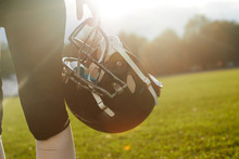 Girl American Football Player Holding Helmet On A Background Of Dawn.