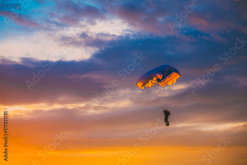 Poster Luchtsport Skydiver On Colorful Parachute In Sunny Sky