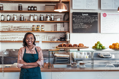 Photo Smiling young African entrepreneur standing at her bakery counter