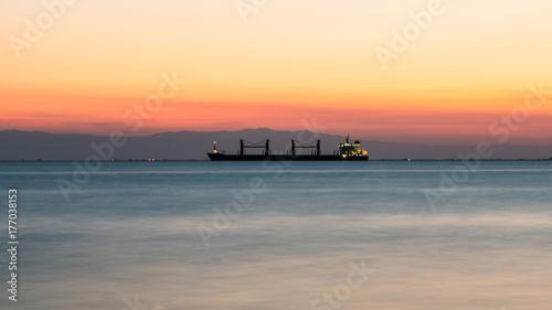 Plakat Spokojna spokojna sceneria morza i wielki statek po zachodzie słońca, w pięknych kolorach