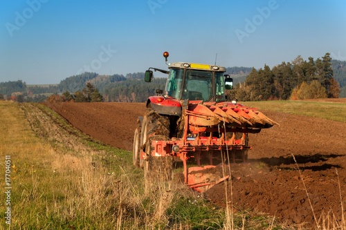 Zdjęcie XXL Pole pole czerwone ciągnika. Jesienna praca w terenie. Życie w gospodarstwie. Krajobraz rolniczy w Republice Czeskiej.