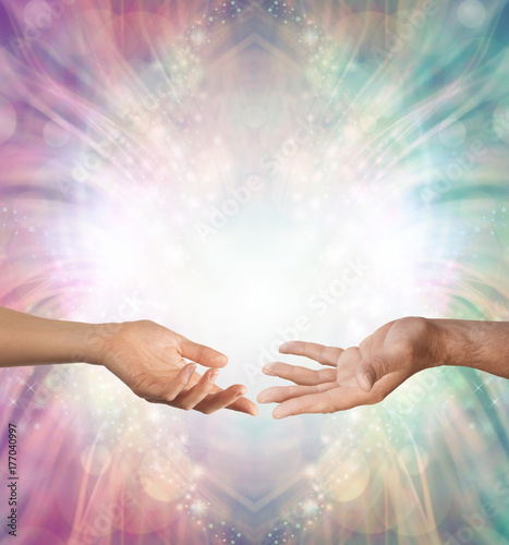 Male and Female energy merging - a female hand and a male hand with open palms facing each other against a beautiful intricate masculine and feminine colored energy background with copy space above