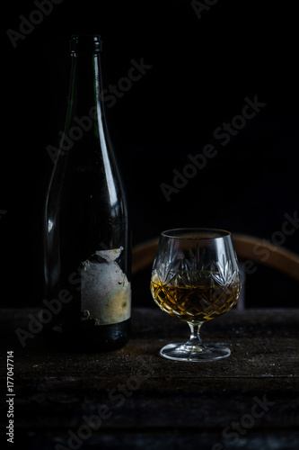 Vintage sherry bottle and crystal glass in natural low light setting.