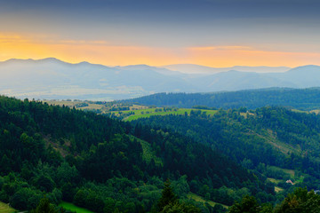 Fototapeta Do hotelu Vast panorama view of foggy valley in the Owl Mountains with silhouette of Sudetes mountain range at dusk. Mountainous countryside landscape in south-west Poland.
