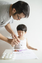 Dad Teaching Son How To Paint