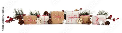 Photo  Christmas border with branches and rustic brown and white gift boxes isolated on