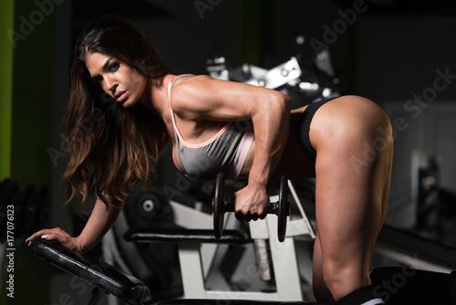 Plakat Kobieta ćwiczy Z powrotem Z Dumbbells W Gym