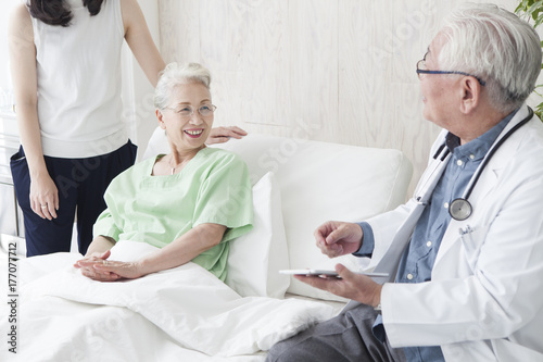 Fotografie, Obraz  Geriatric doctor explaining the situation to the family who came to the hospital
