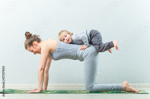 Leinwand Poster hatha yoga exercises mom with child practicing at home