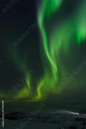 Hills and tundra covered with snow and in the sky the stars, the Aurora Poster