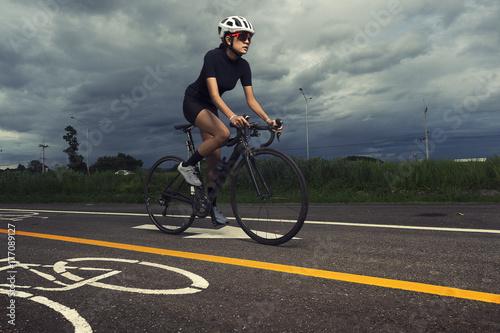Fototapeta Azjatycka zdrowa cyklista dziewczyna jest ubranym hełm Kolarstwo i ćwiczenie na bicyklu w śladzie, otwartej drodze, krzyż proces i miękki flary filtr pracujemy out i sporta pojęcie