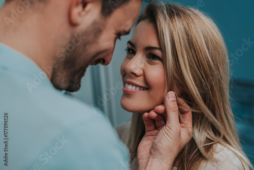 Romantic couple looking at each other and smiling. Wallpaper Mural