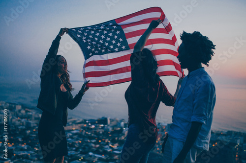 Group of Teenager celebrating with USA flag on mountain