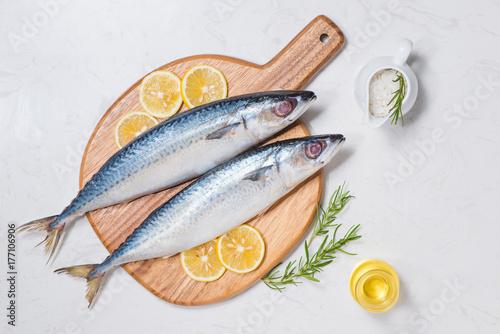 Plakat Naczynie do gotowania ryb z różnych składników. Świeża surowa ryba dekorująca z cytryna plasterkami i ziele na drewnianym stole.