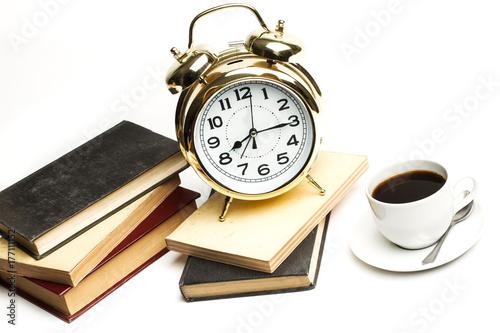 Reloj dorado despertador retro con libros apilados y taza de café sobre fondo blanco aislado. Vista de frente y superior