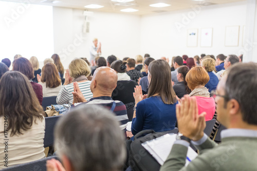 Tuinposter Vliegtuig Life coaching symposium. Female speaker giving interactive motivational speech at entrepreneurship workshop. Audience in conference hall. Rear view of unrecognized participant.