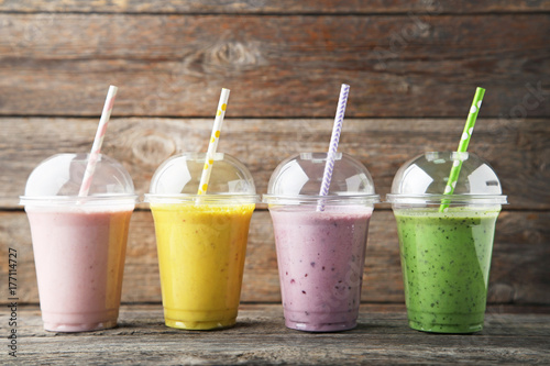 Sweet smoothie in plastic cups on grey wooden table
