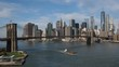 A daytime wide establishing shot of the Manhattan Skyline with a barge traveling under the Brooklyn Bridge.