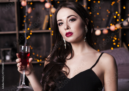 Young beautiful sexy brunette woman wearing black evening dress with decollete, makeup with red lips and hairstyling sitting with a glass of wine .