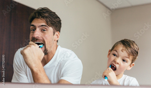 Father and son brushing teeth in bathroom Canvas-taulu