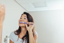 Woman Brushing Teeth In The Ba...