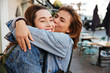 canvas print picture - Close-up photo of two emotional happy woman friends hugging each other on city street
