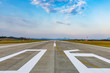 canvas print picture - Runway, airstrip in the airport terminal with marking on blue sky with clouds background. Travel aviation concept.