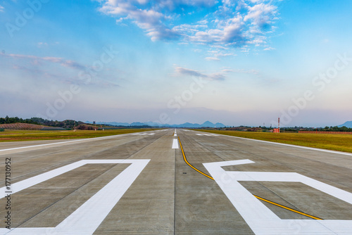 Runway, airstrip in the airport terminal with marking on blue sky with clouds background. Travel aviation concept.