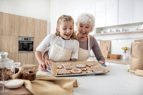 Fotografía  Happy senior woman enjoying baking process with her granddaughter