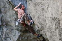 Muscular Rock Climber Concentrating On A Hard Move