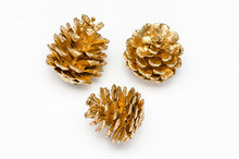 Three Golden Pine Cone On A White Background