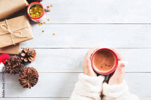 Foto op Plexiglas Chocolade female hand holding cup of hot cocoa or chocolate with Christmas present on wooden table from above