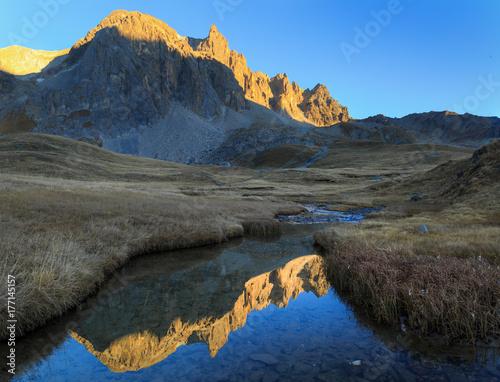 Zdjęcie XXL Górskie szczyty refelcted w małym strumieniu podczas jesiennego zachodu słońca.