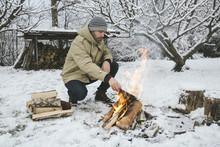 Man Adding Wood To A Bonfire I...