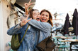 canvas print picture - Photo of two charming brunette female friends hugging each other, showing peace sign, looking at camera on city street