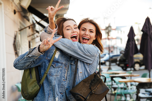 Photo of two charming brunette female friends hugging each other, showing peace sign, looking at camera on city street