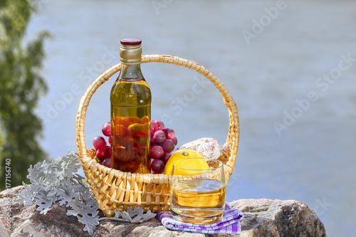 Plakat Butelka ze szkłem whisky i kosz z owocami na skale nad rzeką