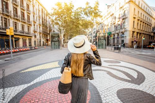 Fototapeta premium Młodej kobiety turystyczny odprowadzenie z powrotem na środkowej ulicie z sławnymi kolorowymi płytkami w Barcelona mieście