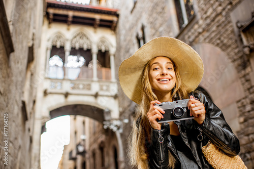Young woman tourist in hat standing with photo camera in front of the famous bri Canvas Print