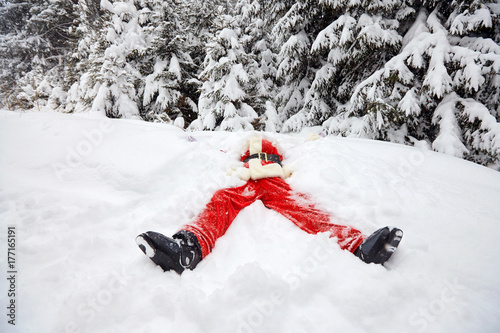 Fotografia, Obraz  Santa Claus lies on the snow in winter for Christmas.