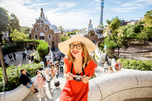 Foto op Canvas Barcelona Woman tourist in red dress having fun visiting famous Guell park in Barcelona