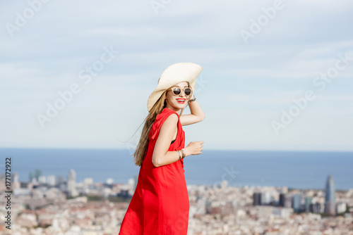 Photo  Young woman tourist in red dress with hat enjoying great cityscape view on Barce