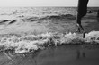 Girl jumping waves in monochrome
