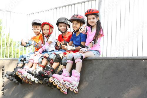 Cute kids on rollers sitting in skate park