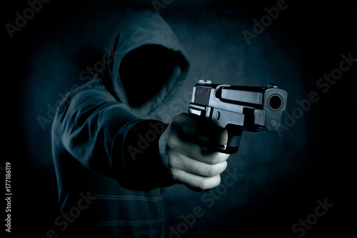 Fotografia Hooded man with a gun in the dark