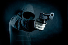 Hooded Man With A Gun In The D...