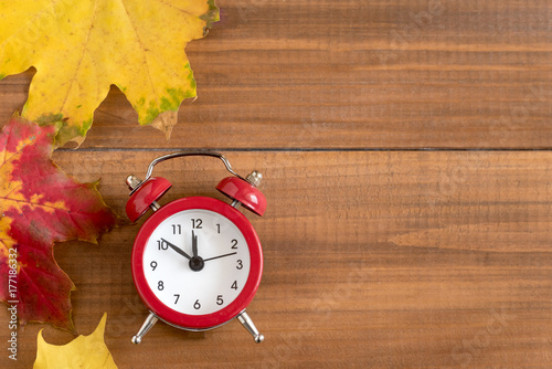 Poster Pays d Asie Top view of red vintage alarm clock on wooden background. Time change concept.