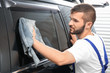 Worker wiping car window after tinting in shop