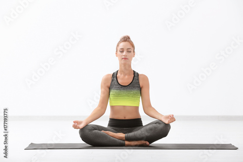Beautiful young woman practicing yoga indoors