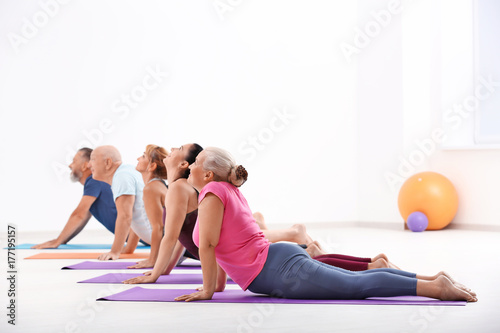 Group of mature men and women at yoga lesson indoors